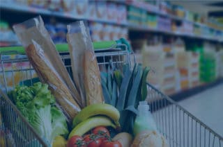 Full shopping cart in the supermarket with blue filter