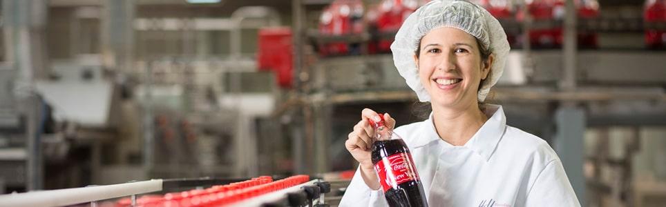 pracovníčka vo výrobnej hale, ktorá drží v rukách fľašu Coca-cola znázorňujúca implementačný proces