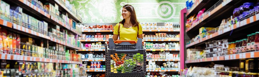 mladá žena s nákupným košíkom v potravinách vo význame pozor na vypredanie zásob