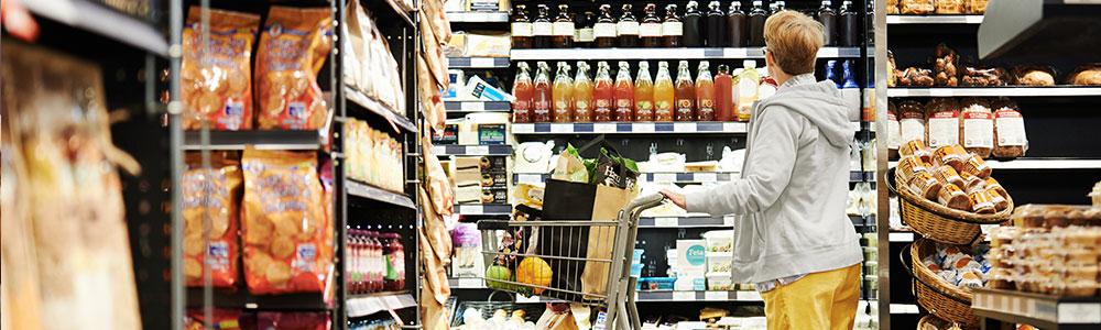 osoba s nákupným košíkom v predajni s potravinami vo význame EDI a Žabka
